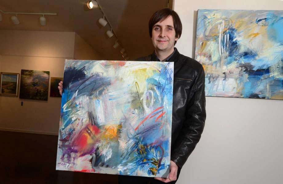 "Artist Bruce Horan with two of his abstract paintings that will be featured in the Rowayton Arts Center's upcoming exhibition ""Abstraction"" and on view during Slow Art Day 2017. Photo: Erik Trautmann / Hearst Connecticut Media"